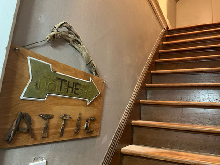 "Tacoma Corporate Rental - Sign says ""RThe Attic"" pointing up a set of wooden stairs"